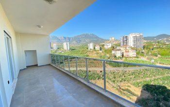 Новые светлые апартаменты 3+1 с панорамным видом в Махмутлар
